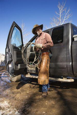 pickup truck: Hombre de pie con un lariat junto a la puerta abierta de una camioneta pickup. Un disparo vertical.  Foto de archivo
