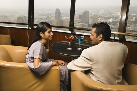 lounge: Young adult male and female seated near window in a high rise restaurant. They are smiling at one another. Horizontal shot. Stock Photo