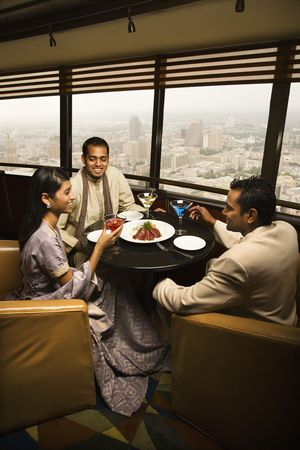 High angle view of young adult males and a female seated near a window in a high rise restaurant. Vertical shot. photo
