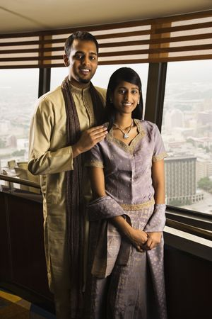 Portrait of a young adult couple standing near a high rise window and smiling at the camera. Vertical shot. Stock Photo - 6429008