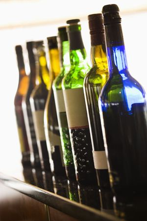 tilted view: Tilted view of a row of assorted colorful wine bottles. Vertical shot. Stock Photo
