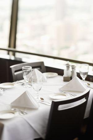 ハイアングルビュー: 場所の設定と白いテーブル クロスのレストランのテーブルの高角度のビュー。 テーブルは、ウィンドウでは。垂直方向のショット。