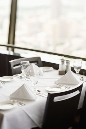 High angle view of a restaurant table with place settings and a white tablecloth.  The table is by a window. Vertical shot. Stock Photo