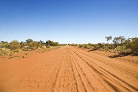 Desert road in the remote Australian Outback. Tread marks can be seen imprinted in the dirt. Horizontal shot.