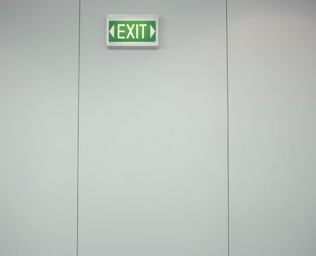 Low angle view of a green, lighted exit sign on a gray wall. Horizontal shot. photo