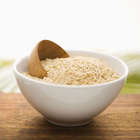 White ceramic bowl containing rice and a wooden cup. The bowl is on top of a wood surface, and a palm frond is in the background. Square format. Isolated on white. photo