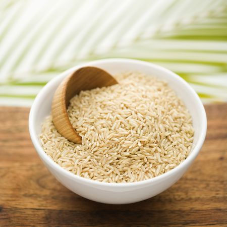 palm frond: Ciotola di ceramica bianca contenente riso e una tazza di legno. La ciotola � in cima a una superficie di legna e una fronda palm � in background. Formato quadrato. Archivio Fotografico