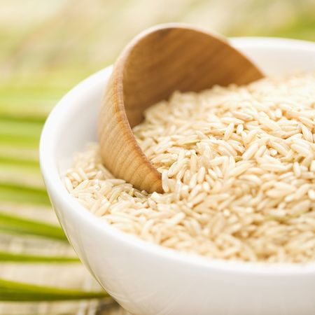 brown rice: Cropped close-up of a white ceramic bowl containing rice and a wooden cup. There is a palm frond in the background. Square format.