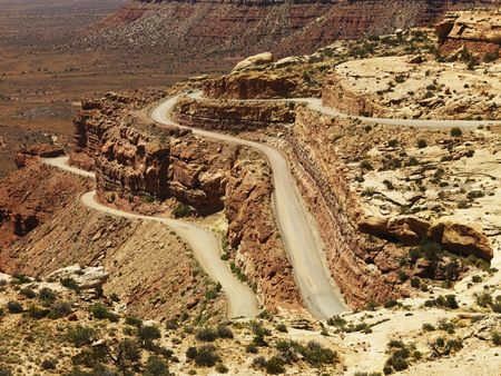 High angle view of a winding dirt road on a desert rock formation. The surrounding landscape is visible in the background. Horizontal shot. photo