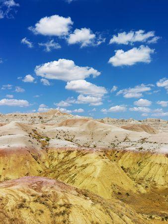 rugged terrain: Rugged terrain in Badlands National Park, South Dakota, beneath blue sky and clouds. Vertical shot. Stock Photo