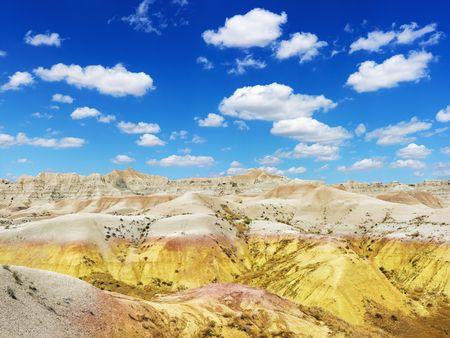 rugged terrain: Rugged terrain in Badlands National Park, South Dakota, beneath blue sky and clouds. Horizontal shot.