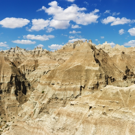 Mountain terrain in Badlands National Park, South Dakota, beneath blue sky and clouds. Square format. photo