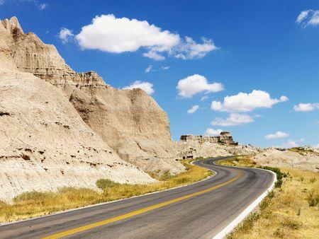 south dakota: Strada rurale da formazioni rocciose e un campo di Malelande National Park, South Dakota. Tiro orizzontale.  Archivio Fotografico