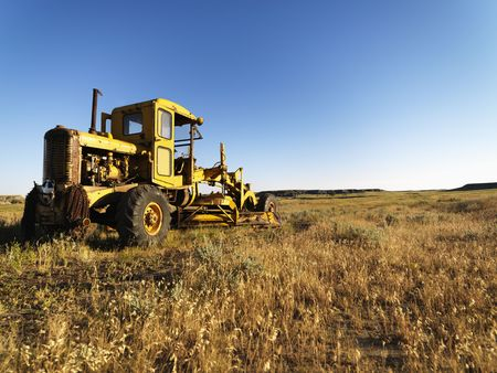 grader: Old grader in a field in the country. Horizontal shot. Stock Photo