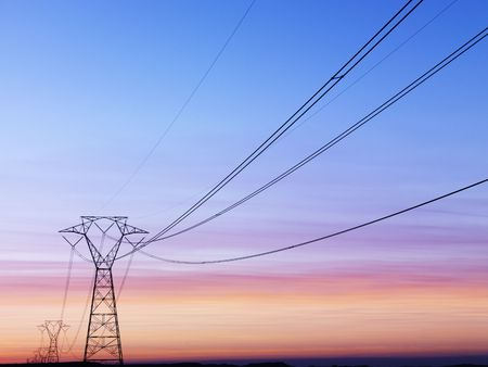 Line of electrical towers and power lines at sunset. Horizontal shot.
