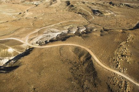 Aerial view of a of rural, desert landscape with a road running through it. Horizontal shot.