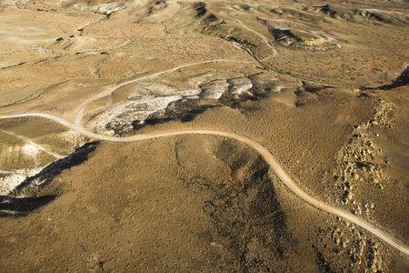 high desert: Aerial view of a of rural, desert landscape with a road running through it. Horizontal shot.