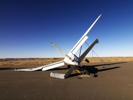 crashed: A small, crashed aircraft in a desert landscape. It is on its side with a broken wing and tail. Horizontal shot.