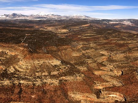 craggy: Aerial view of an arid, craggy landscape with mountains in the background. Horizontal shot.