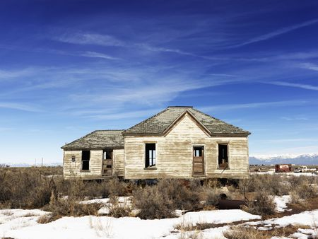 An abandoned home in the remote countryside. Snow and shrubs cover the ground. Horizontal shot. photo