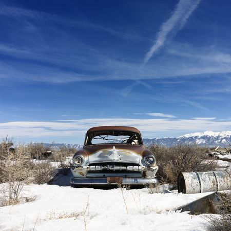 A deserted classic automobile in the remote countryside with snow on the ground. Horizontal shot. Stock Photo