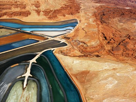tailings: Aerial view of an arid, craggy landscape surrounding tailing ponds. Horizontal shot.