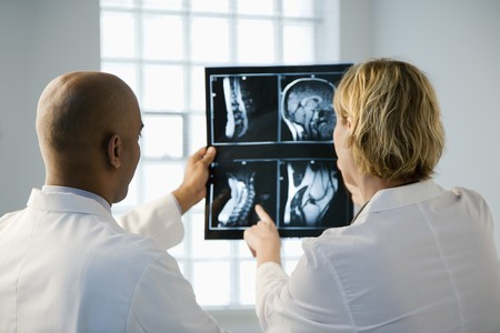 Male and female doctor looking at patient xray film.