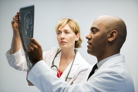 Male and female physicians holding and looking at patient xray film. Standard-Bild