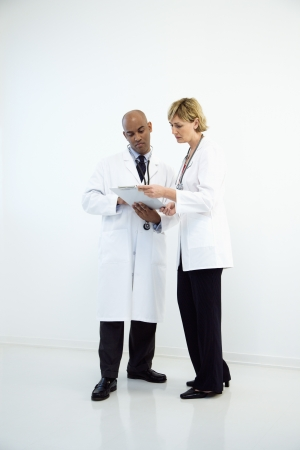 two people talking: Male and female doctors looking at medical chart.