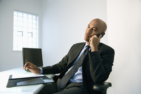 African American businessman sitting at office desk talking on cellphone.