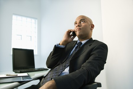 African American businessman holding cellphone to ear looking bored.