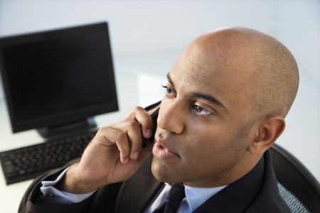 African American businessman sitting at office desk on cellphone.