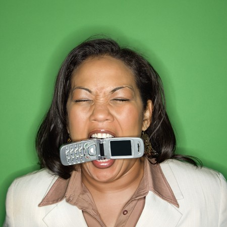 Portrait of African American businesswoman biting cellphone. photo