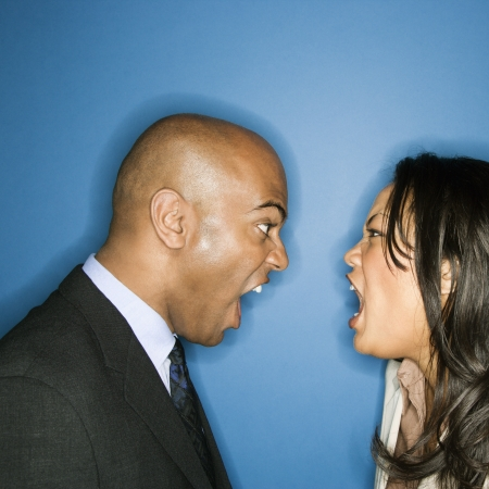 Businessman and businesswoman face to face yelling at eachother.