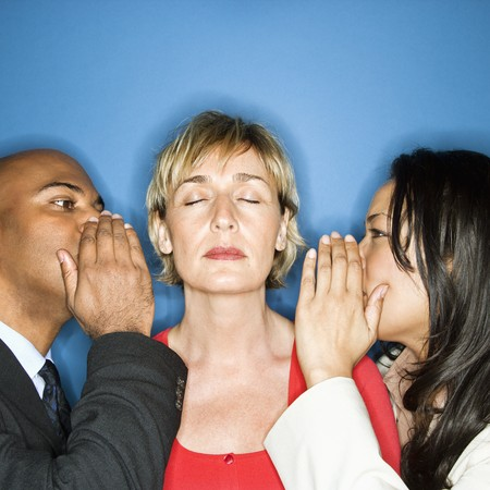 Businesspeople whispering into each ear of businesswoman. photo