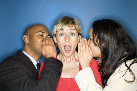 Businesspeople whispering into each ear of businesswoman as she looks shocked.