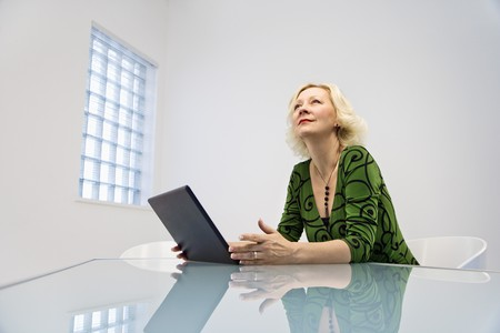 Caucasian middle aged businesswoman in office working on laptop computer. photo