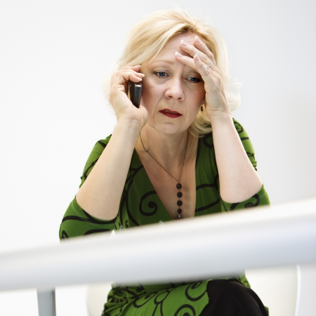 Caucasian middle aged businesswoman in office on cellphone looking stressed and upset. Standard-Bild
