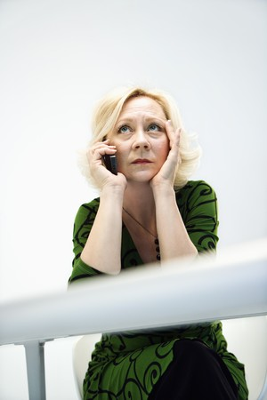 Caucasian middle aged businesswoman in office on cellphone looking stressed and upset. photo