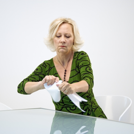 disgruntled: Caucasian middle aged businesswoman sitting at office desk ripping paperwork.