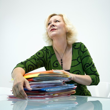 Caucasian middle aged businesswoman sitting at office desk with pile of folders. Stock Photo - 6908448