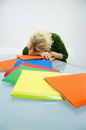 Caucasian middle aged businesswoman sitting at office desk with head down on top of pile of folders. photo