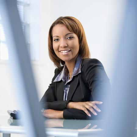 Portrait of African American Businesswoman sitting at Office Desk lächelnd.