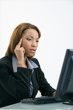 Portrait of African American businesswoman sitting at office desk working on computer. photo