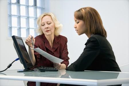 Businesswomen sitting at office desk going over paperwork.