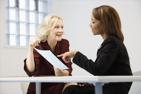 review: Businesswomen sitting at office desk going over paperwork pointing and smiling.