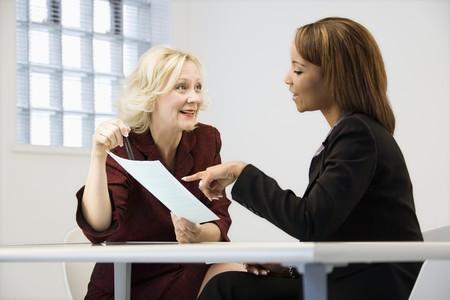 dos personas conversando: Empresarias sentado en el escritorio de Oficina que va sobre el papeleo apuntando y sonriente.
