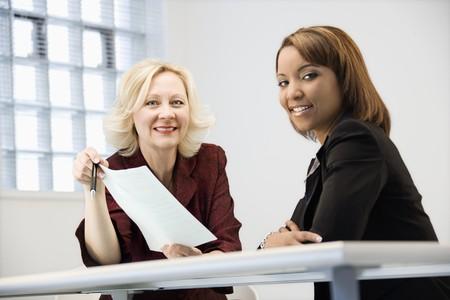 Businesswomen sitting at office desk going over paperwork. photo