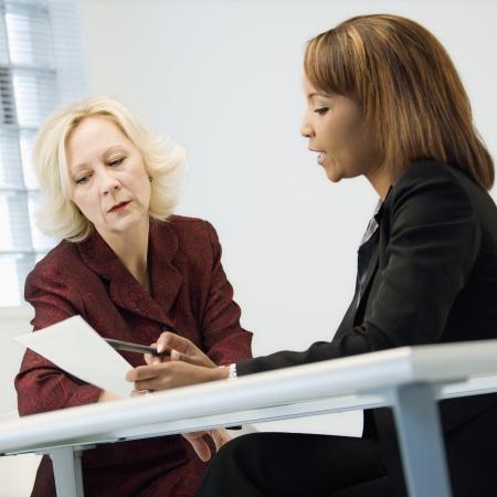 dos personas conversando: Empresarias sentado en el escritorio de oficina discutiendo el papeleo.
