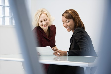Businesswomen sitting at office desk discussing paperwork smiling. Stock Photo - 6908659